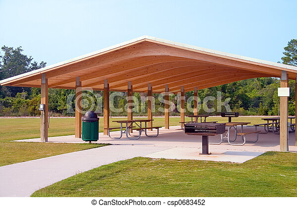 Picnic tables and grill under wood roof structure in local park