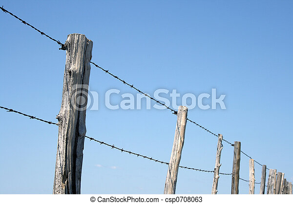 Barbed wire farm fence against blue sky - csp0708063