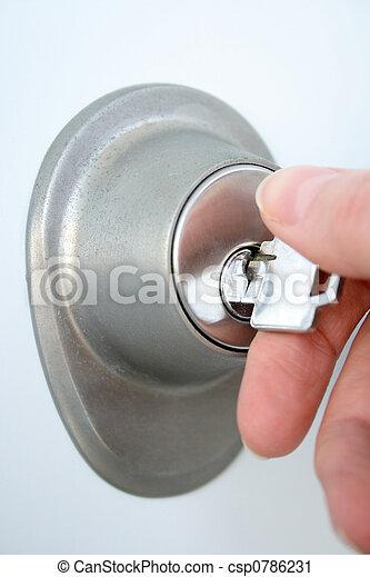 Hand unlocking the door with a key - csp0786231