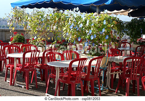 Outdoor restaurant with chairs and tables flowers