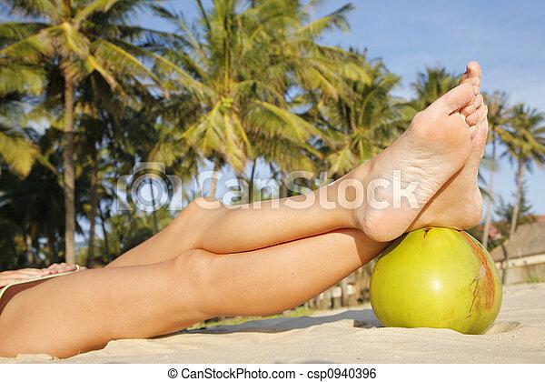 Women\\\'s feet on green coconut on tropical beach