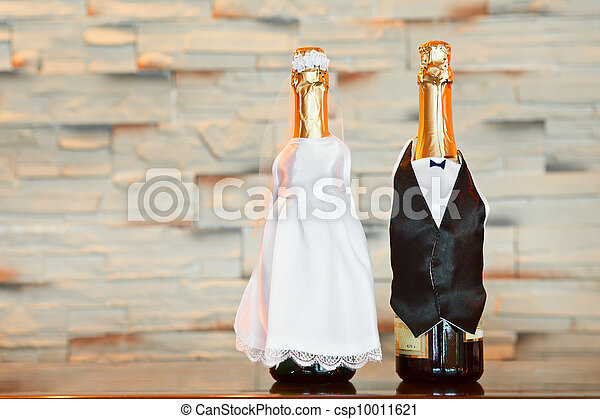 Two bottles of champagne in bride and groom clothes in table. Copy space - csp10011621
