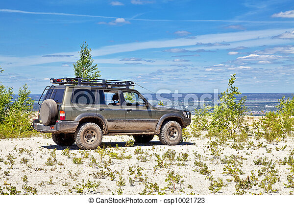 All-wheel drive SUV on the edge of a cliff in a quarry rubble. Against the background of blue sky. - csp10021723