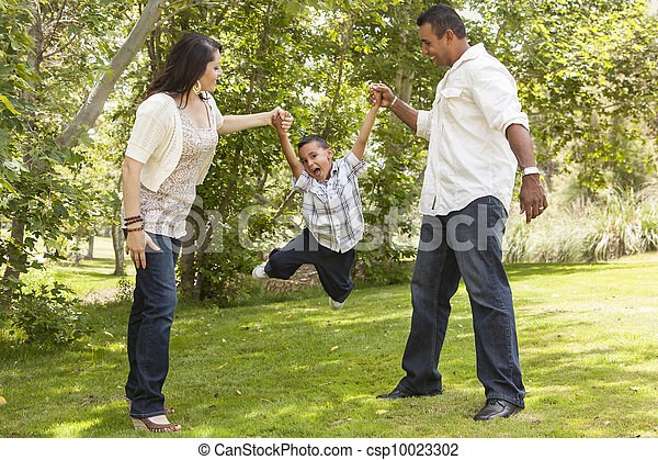 Hispanic Mother and Father Swinging Son in the Park - csp10023302