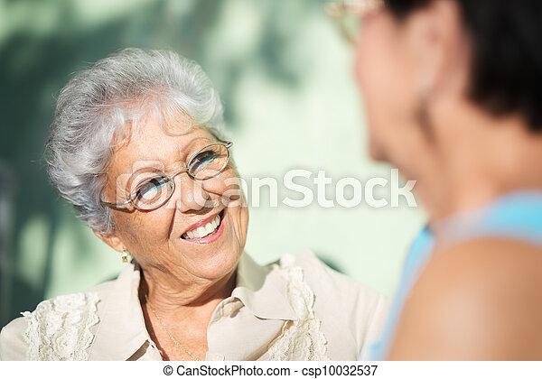 Old friends, two happy senior women talking in park - csp10032537