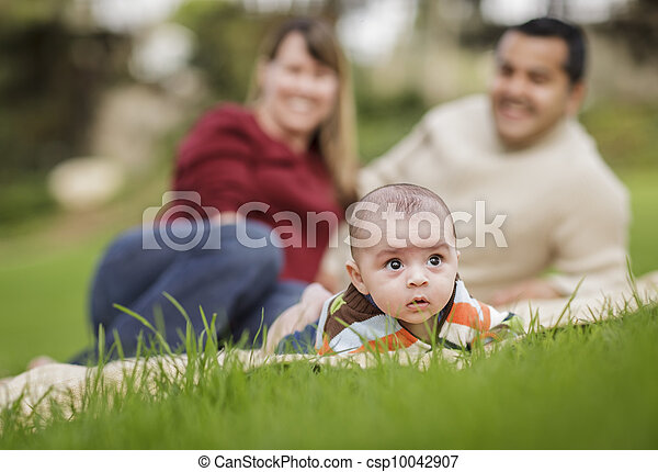 Happy Mixed Race Baby Boy and Parents Playing in Park - csp10042907