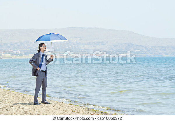 Man with umbrella on seaside beach - csp10050372