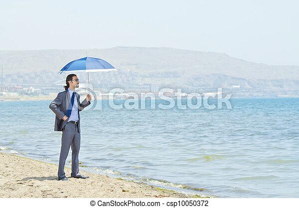 Man with umbrella on seaside beach - csp10050372