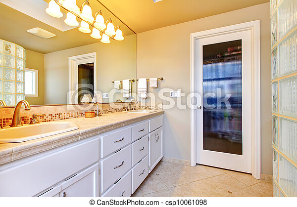 Large bathroom with white cabinets and glass shower. - csp10061098
