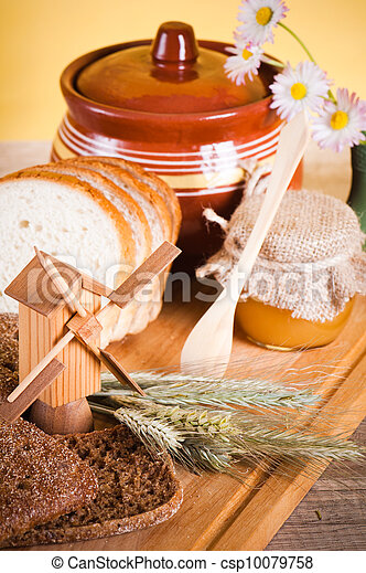 honey, flowers, spike and bread on table  - csp10079758