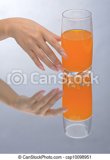 Hand holding glass of orange fluid - csp10098951