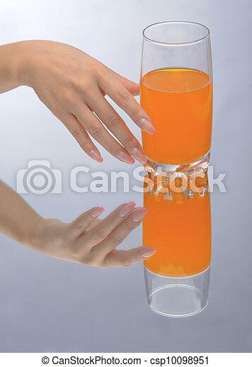 Hand holding glass of orange fluid - csp10098951