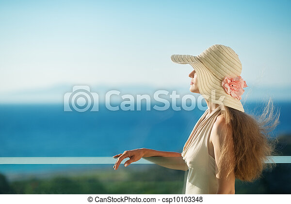 Woman looking on sea from balcony. Rear view