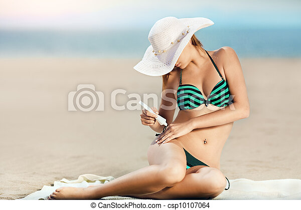 Portrait of woman taking skincare with sunscreen lotion at beach - csp10107064