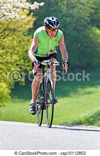 senior riding a bicycle on a road bike - csp10112853