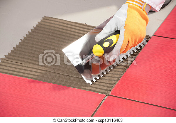 Worker with notched trowel install red tiles with tile adhesive - csp10116463