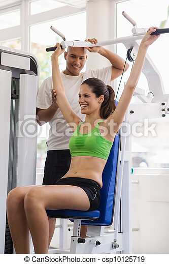 Personal trainer helping woman training in wellness club - csp10125719
