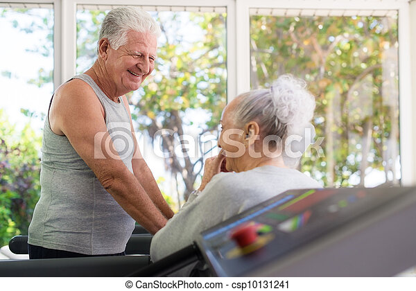 Active senior friends talking and working out in fitness club - csp10131241