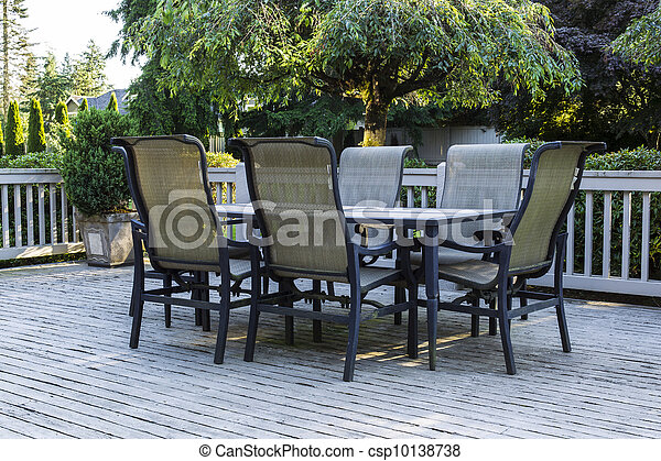 Open outdoor patio, table and chairs with green trees and sky in background