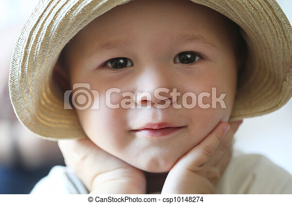 toddler with hands on checks wearing hat and smiling - csp10148274