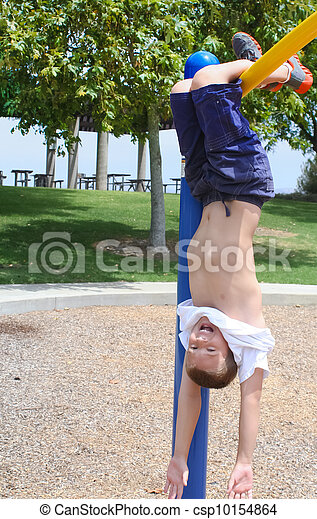 boy hanging upside down in park - csp10154864