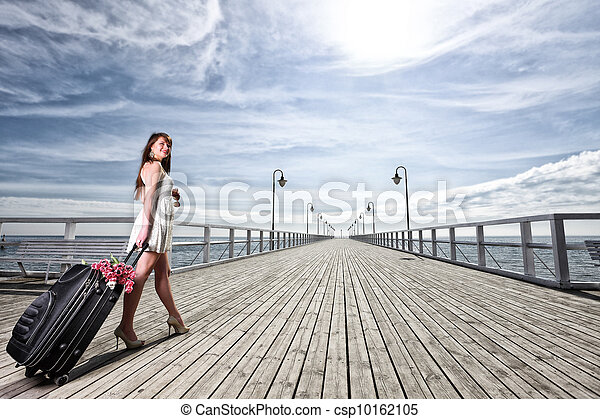 Beautiful woman girl sea mooring suitcase on a pier - csp10162105