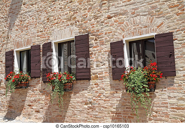 brick wall with windows with shutters and flowers in pots  - csp10165103