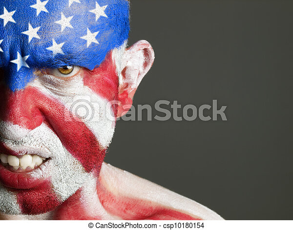 Man with his face painted with the flag of USA. The man is aggressive and photographic composition leaves only half of the face. - csp10180154