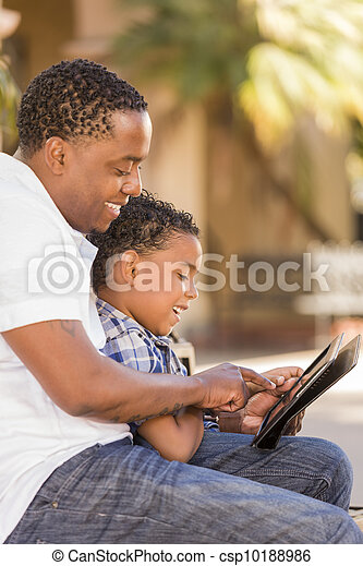 Mixed Race Father and Son Using Touch Pad Computer Tablet - csp10188986