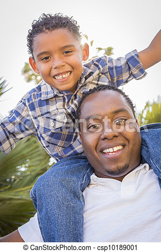Mixed Race Father and Son Playing Piggyback in Park - csp10189001