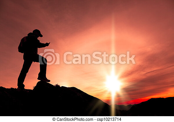 young man using smart phone on the top of mountain - csp10213714