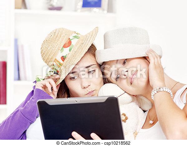 happy teenage girls having fun using touchpad computer - csp10218562