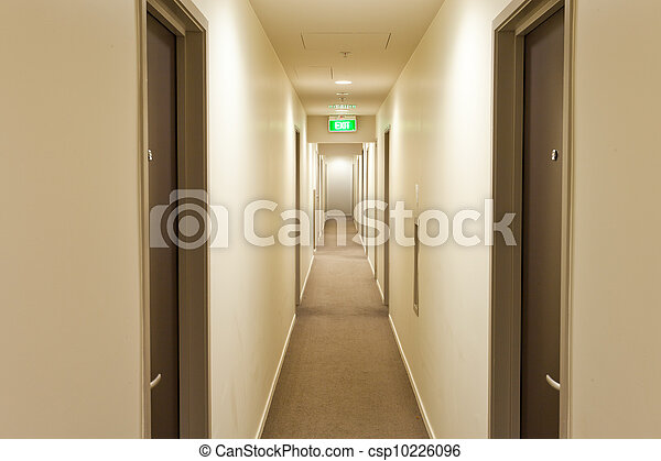 Long corridor with hotel room doors and exit sign - csp10226096