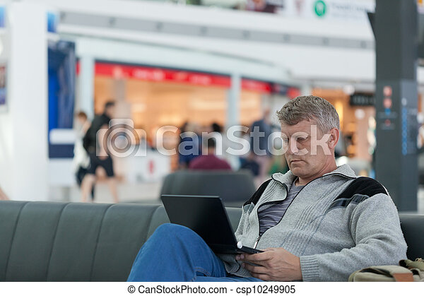 male traveler with the laptop uses a Wi-Fi with expectation of the flight - csp10249905