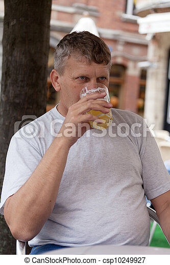 mature man drinks beer in street cafe - csp10249927