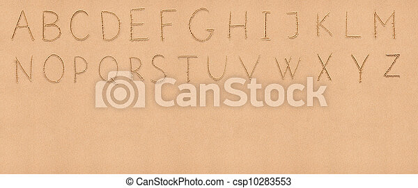 Handwriting English alphabet on flat sand with empty space appropriate as a background for your text - csp10283553