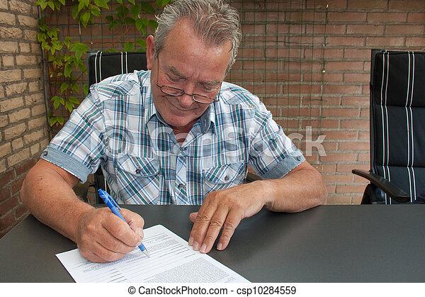 Senior signing a document - csp10284559