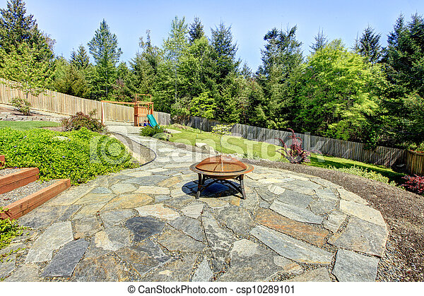 stock photography of fenced backyard with stone and fire