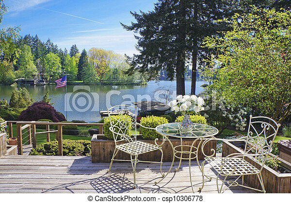 Deck with chairs and table with lake view. - csp10306778