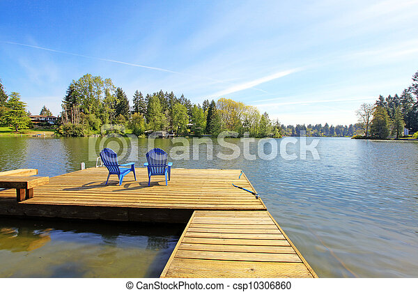 Lake waterfront with pier and two blue chairs. - csp10306860