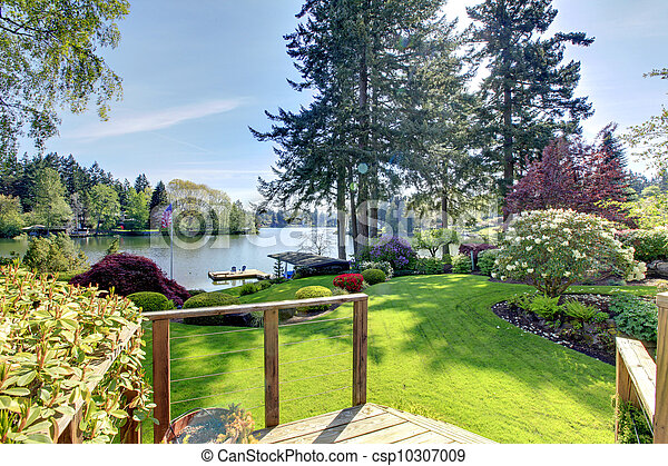 Lake view backyard with deck and spring landscape. - csp10307009