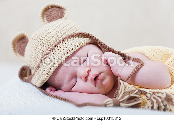 sleeping newborn baby with a ridiculous knitted hat - csp10315312
