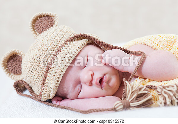 sleeping newborn baby with a ridiculous knitted hat - csp10315372