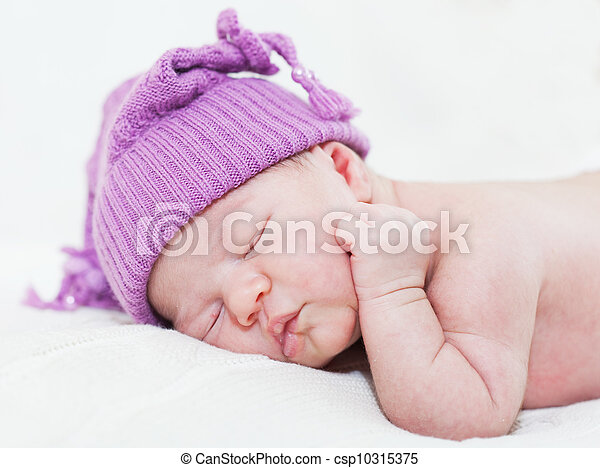 newborn child with a ridiculous violet hat sleeps, lying on a stomach - csp10315375