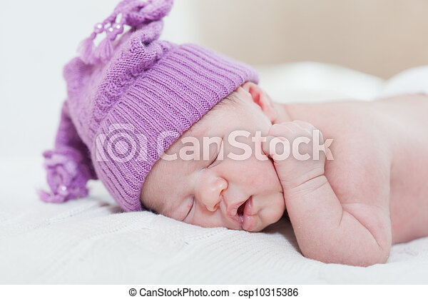 newborn child with a ridiculous violet hat sleeps, lying on a stomach - csp10315386