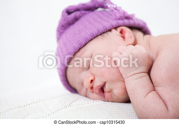 newborn child with a ridiculous violet hat sleeps, lying on a stomach - csp10315430