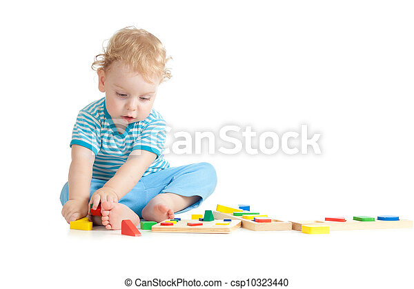 Concentrated child playing logical education toys with great interest on white background - csp10323440