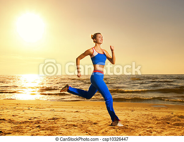 Beautiful young woman running on a beach at sunset (real shot, background is not photoshopped in) - csp10326447