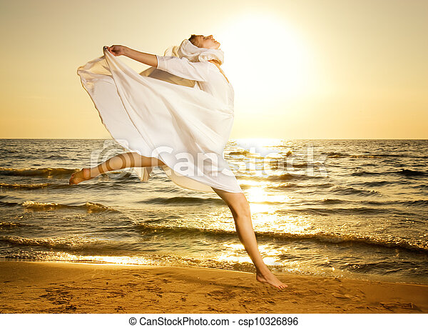Beautiful young woman jumping on a beach at sunset - csp10326896