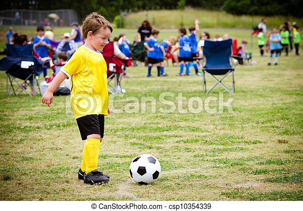 Young child boy playing soccer during organized league game - csp10354339